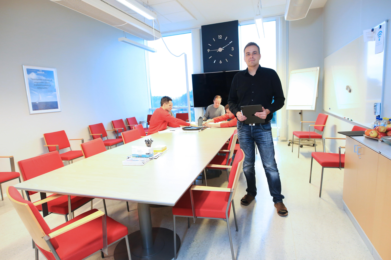 Kuvassa Meriuksen operatiivinen johtaja Toni Uunila poseeraa palaverihuoneessa seisten. Työntekijät istuvat taustalla jutellen.