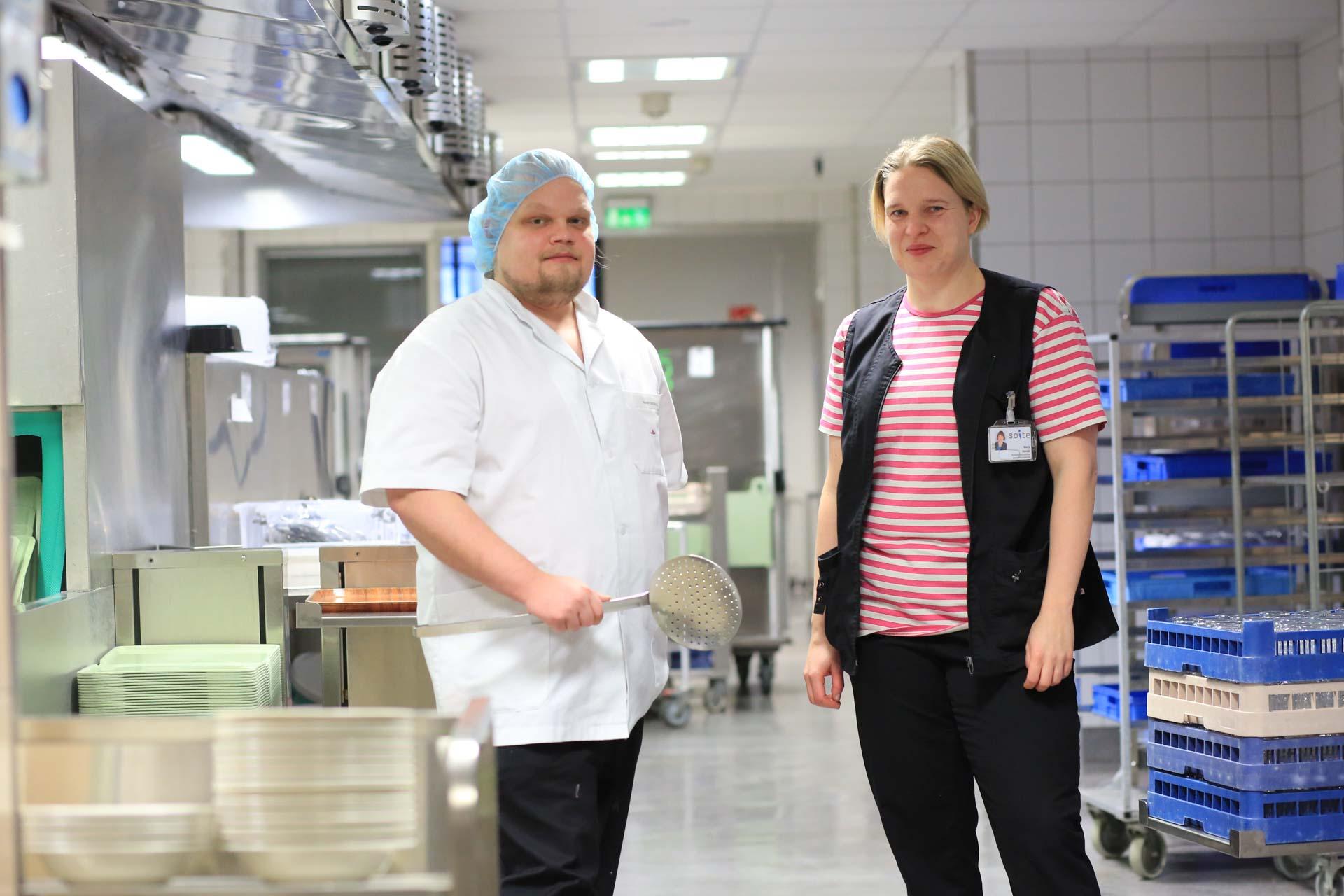 Kuvassa Soiten ruokapalveluiden työntekijät poseeraavat suurkeittiössä.