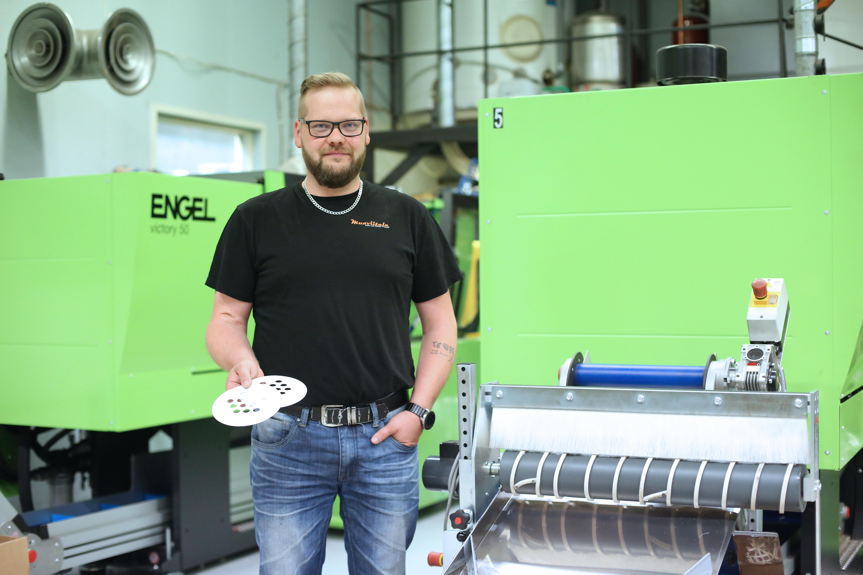 Kuvassa Antti Viitala poseeraa muovialan yrityksen sisätiloissa. Taustalla muovikappaleiden tuotantolaitteita.