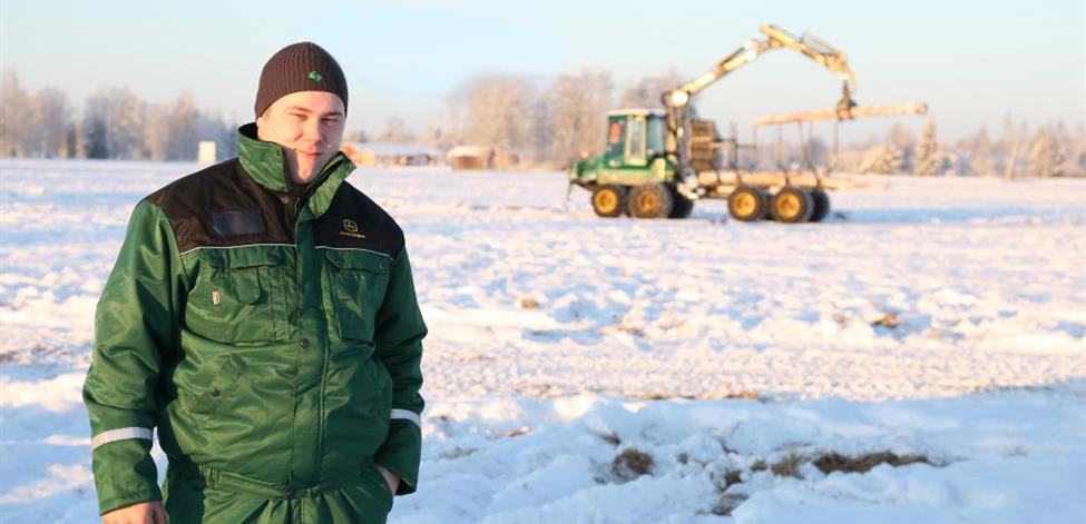 Aku Ojala talvisessa maisemassa taustallaan metsäkone