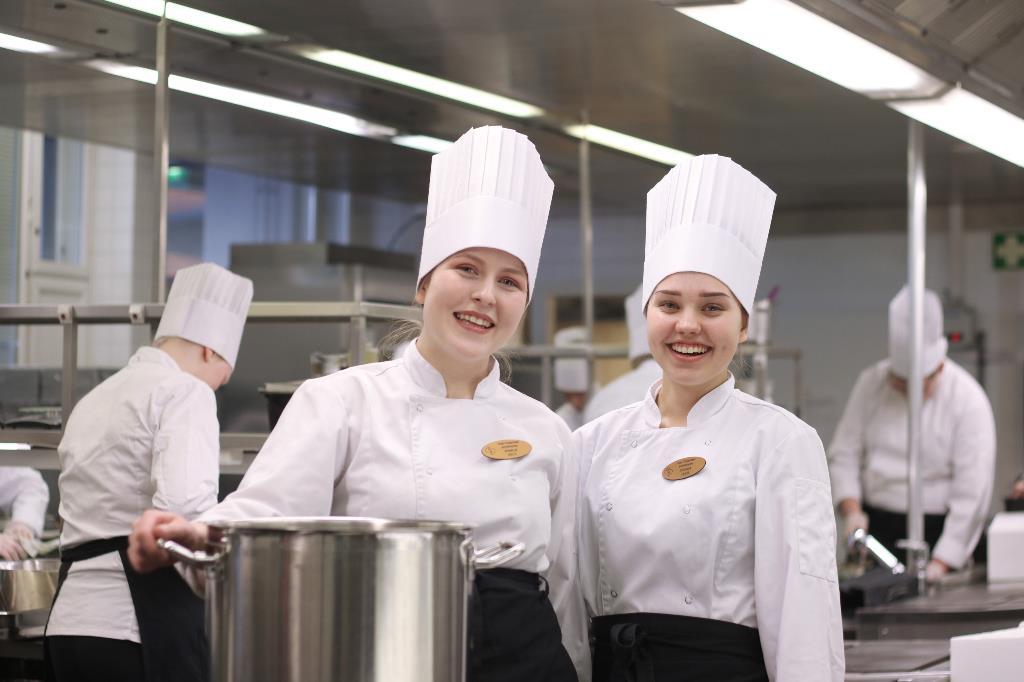 Opiskelijat hymyilevät keittiössä