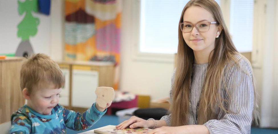 Opiskelija kokoaa palapeliä lapsen kanssa.