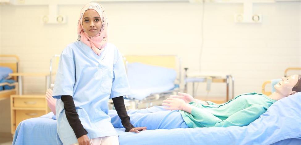 Kuvassa opiskelija istuu sairaalasängyllä ja katsoo kameraan