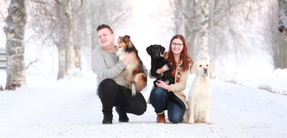 Opiskelijat talvisessa maisemassa kolmen koiran kanssa.