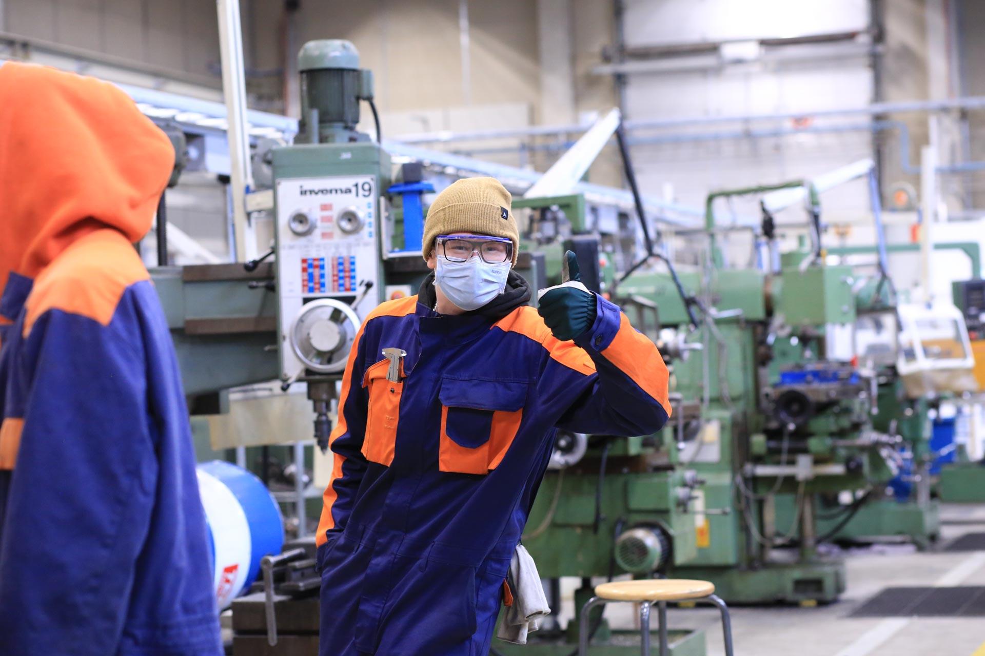 Kone- ja tuotantotekniikka-alan opiskelija poseeraa tuotantohallissa peukkua näyttäen.