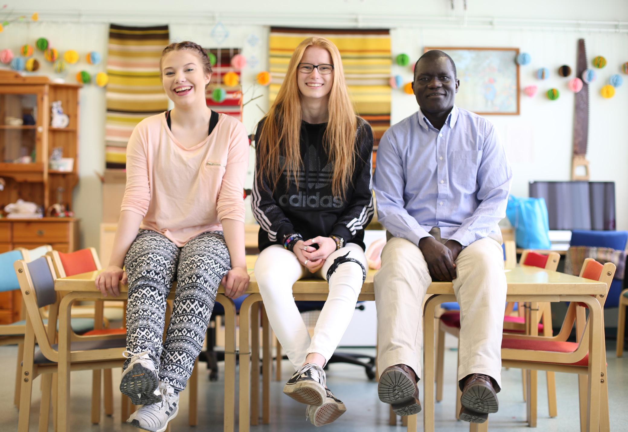Kuvassa opiston opiskelijoita istuu vierekkäin pöydällä