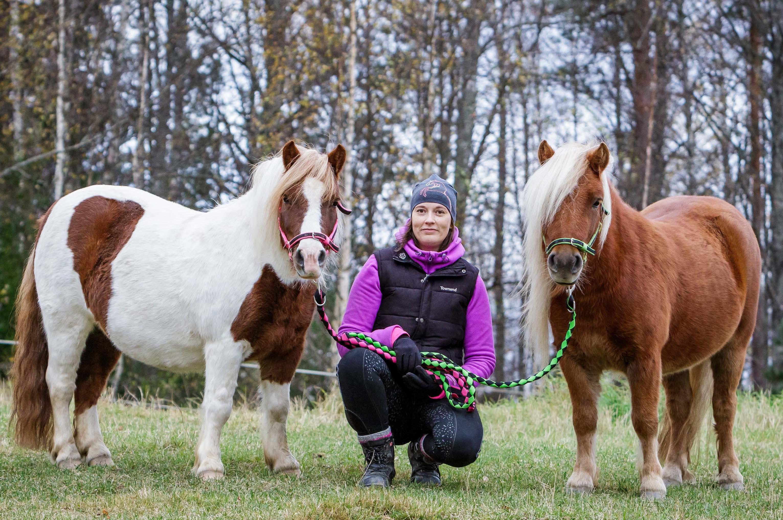 Päivi Kvist poseeraa ponien kanssa kameralle