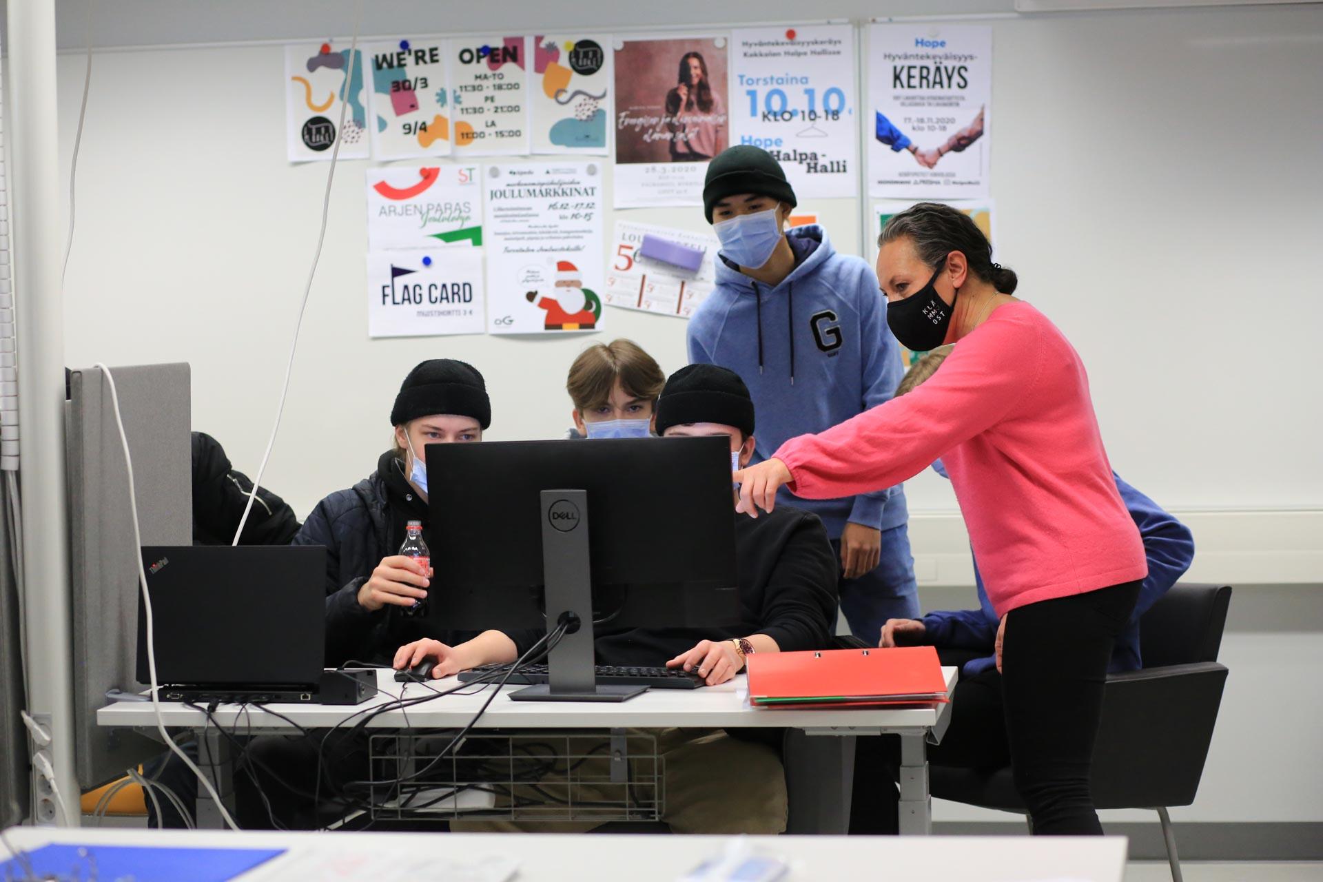 Kuvassa liiketoiminnan opiskelijat työstävät ryhmätyötä istuen ryhmässä tietokoneen ympärillä.