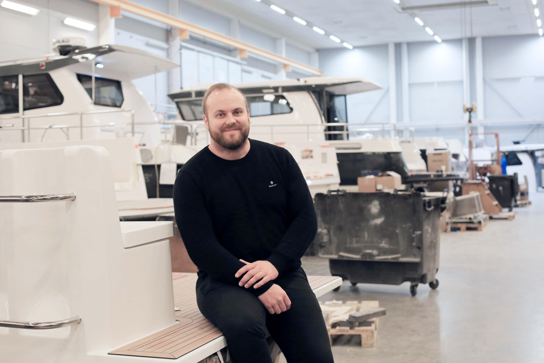 Kuvassa yrittäjä Simon Lindkvist poseeraa tuotantohallissa istuen.