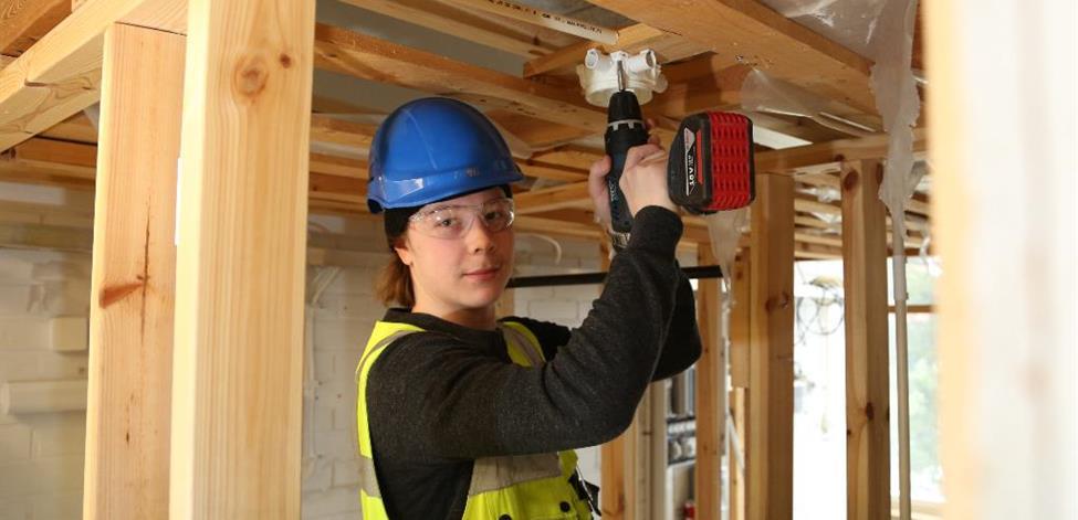 Kuvassa Miikka asentaa sähköjä rakennuskohteessa