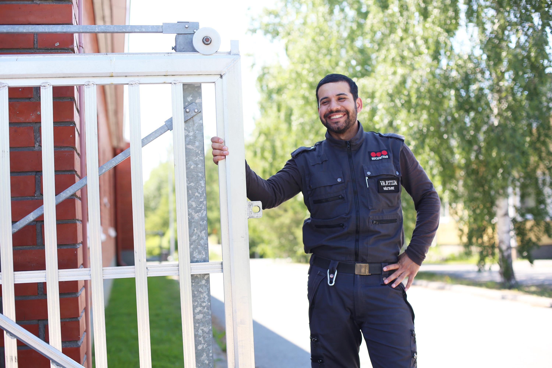 Kuvassa vartijaksi valmistunut Mohammed Hoseini poseeraa ulkona portin vieressä.