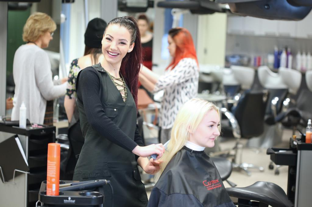 Hiusalan opiskelija harjaa asiakkaan hiuksia.