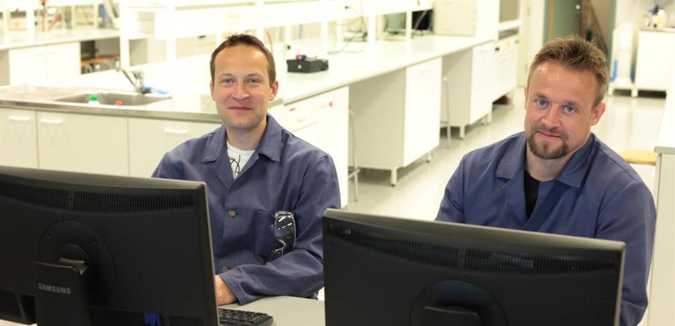 Prosessialan opiskelijat poseeraavat tietokoneiden edessä.