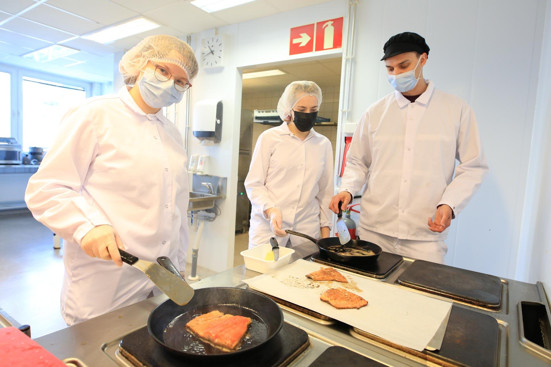 Kuvassa elintarvikealan opettaja Tom Annala ohjeistamassa opiskelijoita.