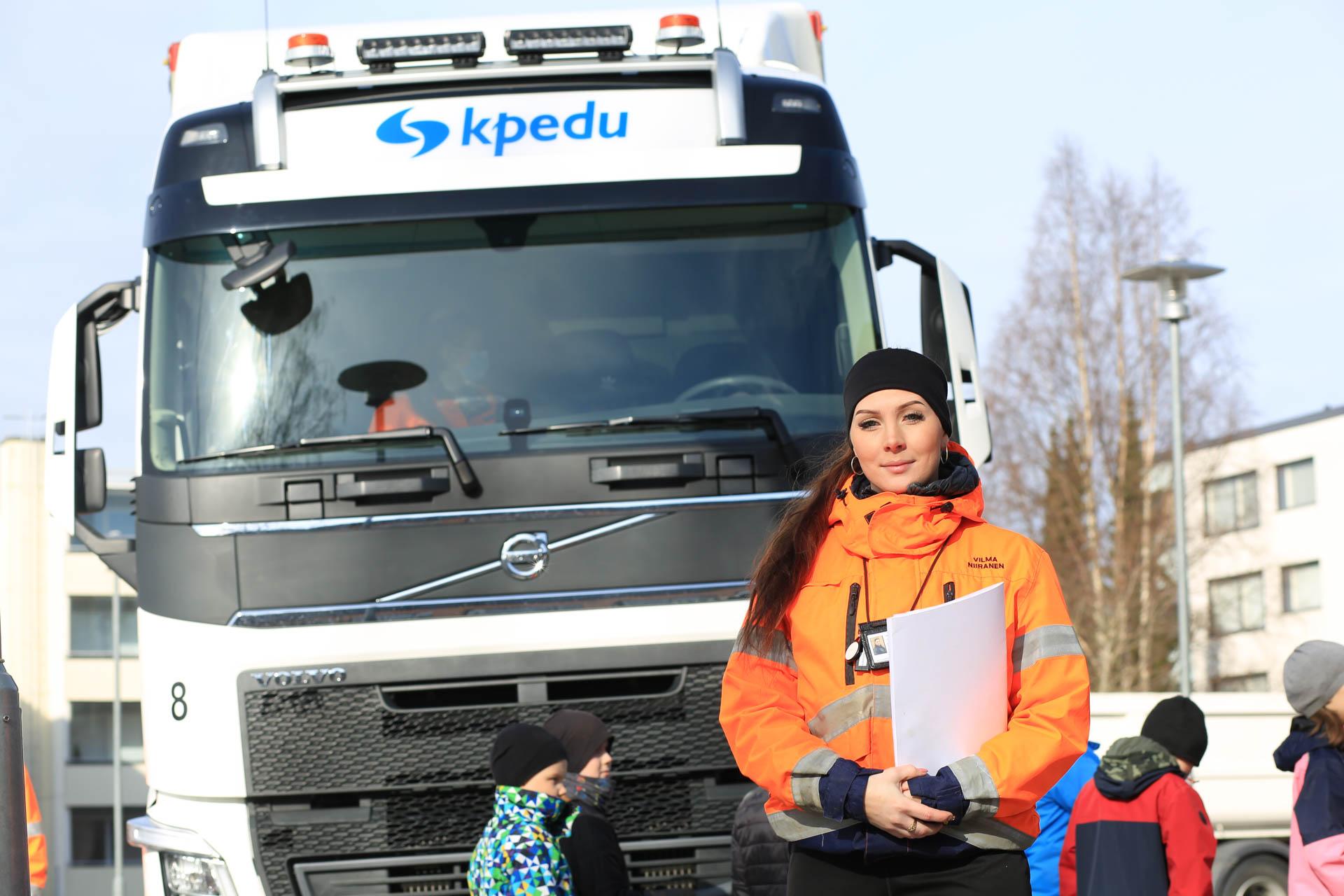 Kuvassa Vilma Niiranen poseeraa kameralle koulun pihalla. Taustalla kuorma-auto ja lapsia.