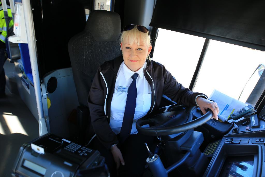 Kuvassa linja-autokuskiksi valmistunut Tarja Partanen poseeraa auton ratissa istuen.
