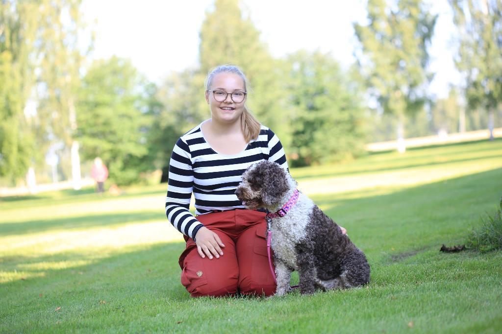 Kuvassa kennelalan opiskelija Siiri Kaskinen poseeraa ulkona istuen koiransa kanssa.
