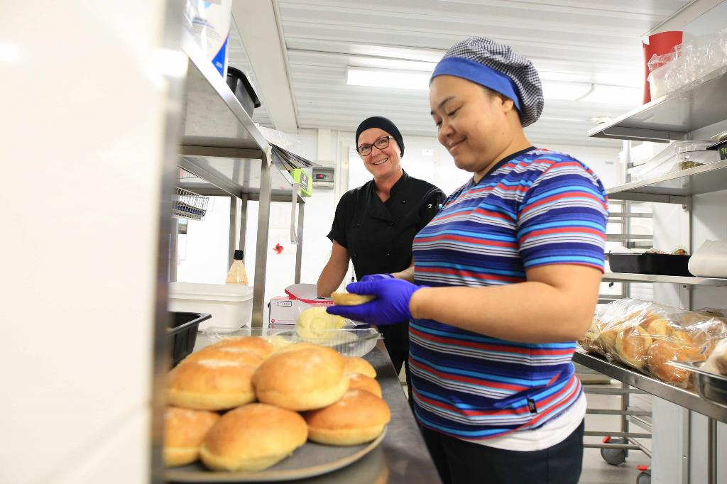 Kuvassa työpaikkaohjaaja Tiina Palosaari ohjaa Jeerawan Kumpakoonia keittiössä.