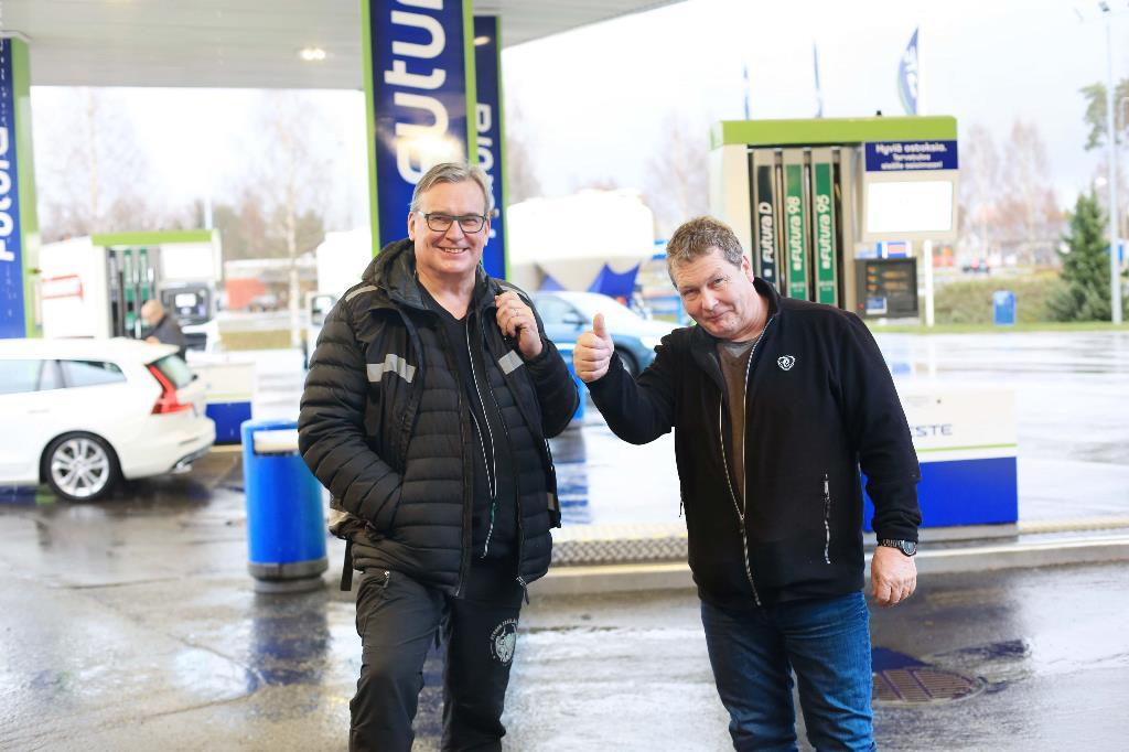 Kuvassa projektipäällikkö Jorma Koivuniemi ja kuljetusalan yrittäjä Jarmo Möttönen poseeraavat huoltoaseman pihalla peukkua näyttäen.