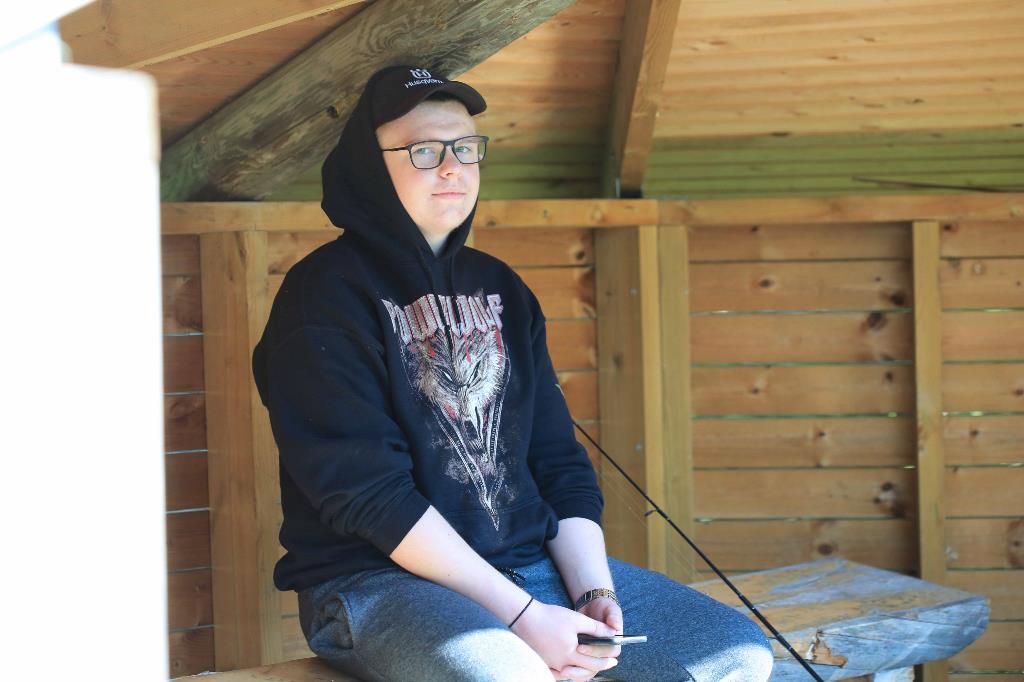 Metsäkoneenkuljettajaksi opiskeleva Verneri Santapakka poseeraa kodassa istuen.